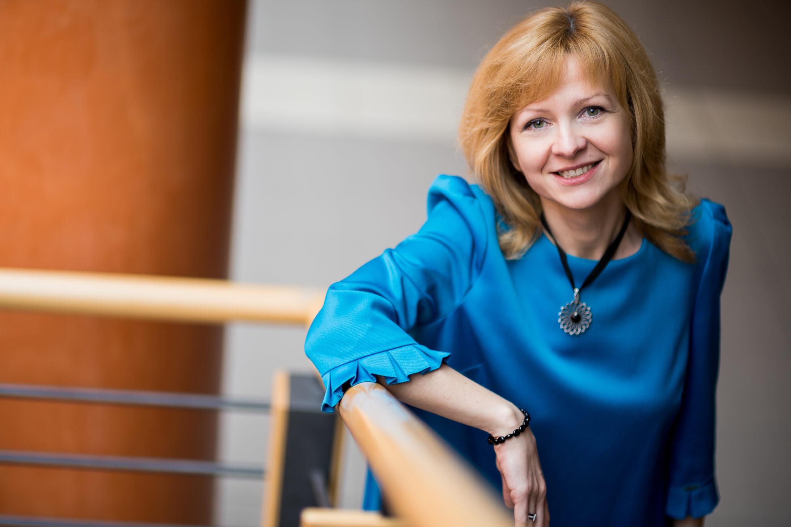 Rozmówczyni, Dominika Kaczorowska-Spychalska, siedzi na schodach. Jest w niebieskiej sukience. Patrzy się w obiektyw.
