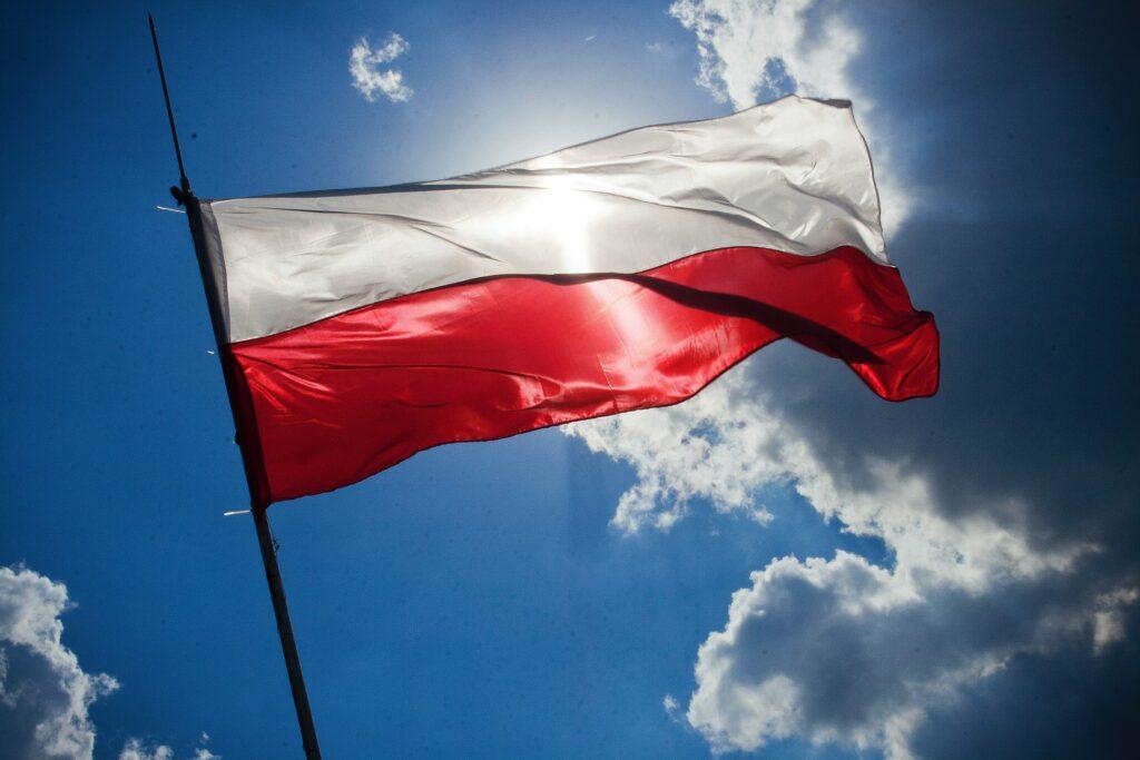 Obraz przedstawiający polską flagę na wietrze na tle błękitnego nieba